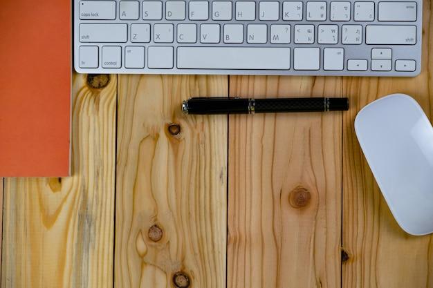 Widok z góry stołu roboczego z keybordem, myszą, notatnikiem