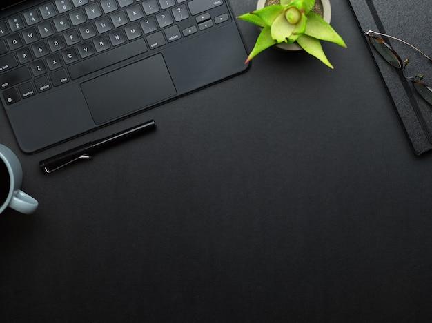 Widok z góry stołu roboczego z klawiaturą laptopa, długopisem, notatnikiem, doniczką i miejscem na kopię w pokoju biurowym