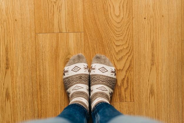 Widok z góry stóp w ciepłych skarpetach na drewnianej podłodze