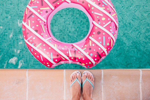 Widok z góry stopy kobiety płasko leżącej kobieta relaksująca się w basenie z różowymi pączkami w gorący słoneczny dzień letnie wakacje sielankowe ciesząc się opalenizną kobieta w bikini na nadmuchiwanym basenie