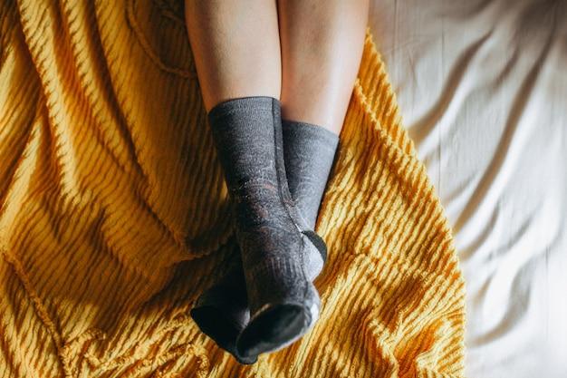 Widok z góry stopy w ciepłych skarpetach na łóżku