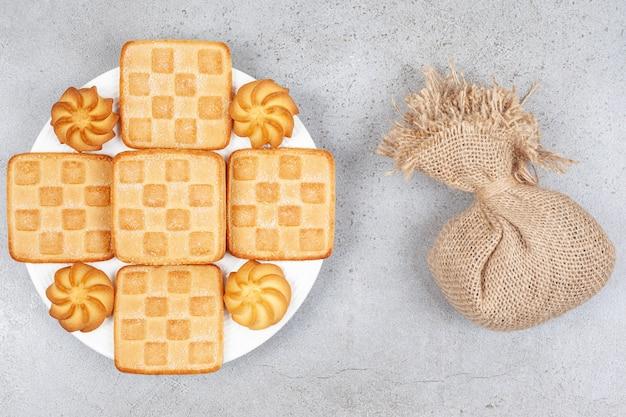 Widok z góry stos ciastek na białym talerzu i worek na szarym stole.