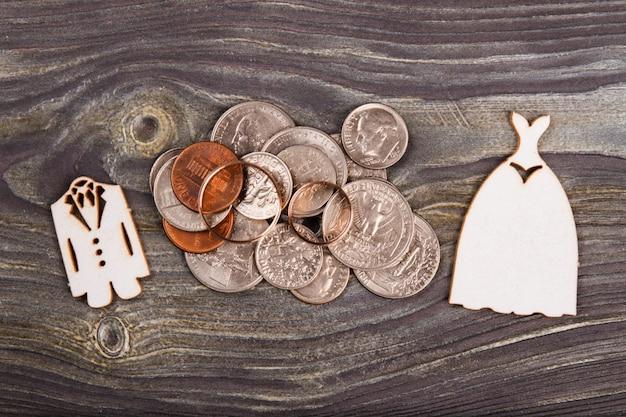Widok z góry stos monet i dwie obrączki ślubne. drewniane biurko tło.