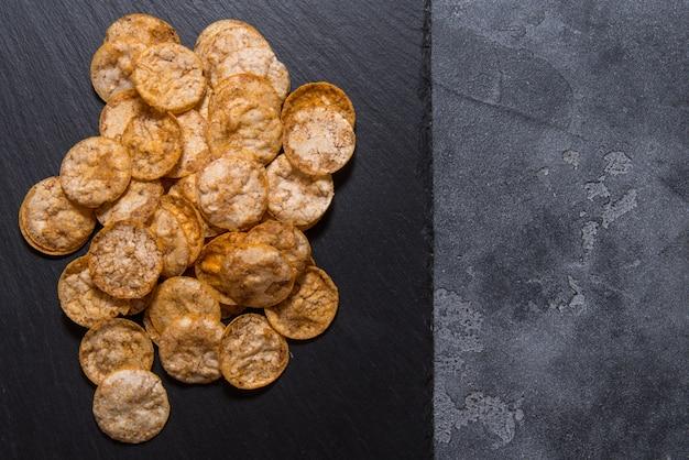 Widok z góry stos organicznych, chrupiące, pieczone, pełnoziarniste chipsy ryżowe z przyprawami. bezglutenowa zdrowa przekąska. na czarnym tle plastry kamienia