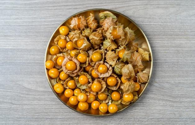 Widok z góry stos owoców agrestu peleryna w złotej płytce.