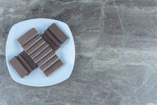 Widok z góry stos wafli czekoladowych na białym talerzu.