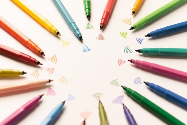 Widok z góry strajków pomalowanych kolorowymi markerami na białym papierze. marekrs wysyłający wi-fi