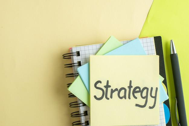 Widok z góry strategia napisana notatka z naklejkami i notatnikiem na kolorowym tle zeszyt kolor wynagrodzenie za pracę biuro szkoła wyższa
