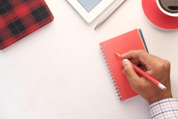 Widok z góry strony człowieka piszącego na czerwonym notatniku ołówkiem