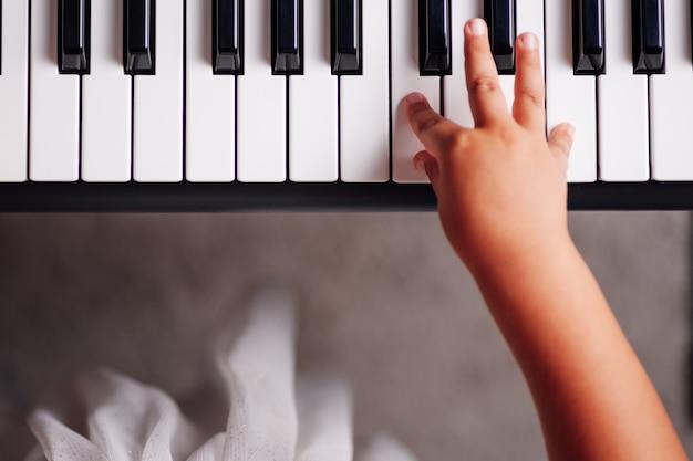 Widok z góry strony dziewczyny naciskając klawisze syntezatora elektronicznego