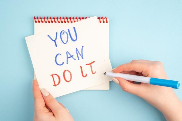 Widok z góry strony kobiety piszącej możesz to zrobić na kartce samoprzylepnej na niebiesko