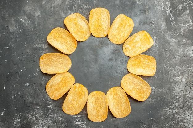Widok z góry strony z przekąskami dla przyjaciół z pysznymi chipsami ziemniaczanymi na szarym stole