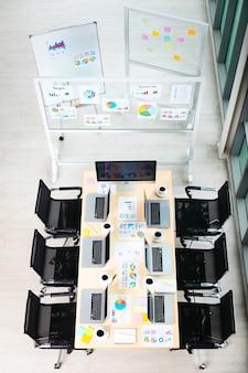 Widok z góry strzał z sali konferencyjnej stół roboczy w pustym biurze firmy pełnym laptopów filiżanki kawy raport danych dokumenty dokumenty czarne krzesła i pusty ekran monitora płyta szklana w pobliżu okien.