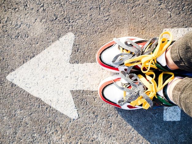 Widok z góry strzałki na asfalcie i butach