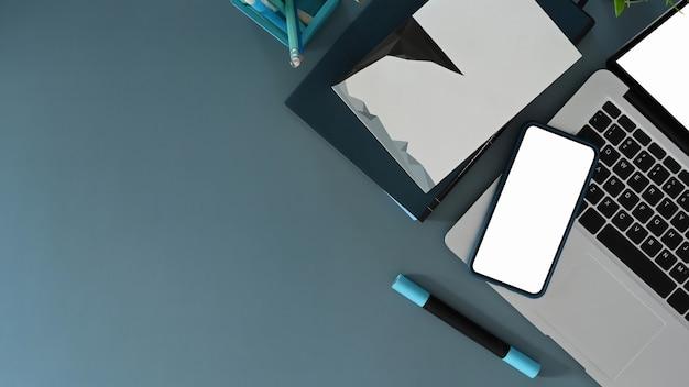 Widok z góry stylowego miejsca pracy z makieta laptopa, smartfona i miejsca na kopię na niebieskim tle.
