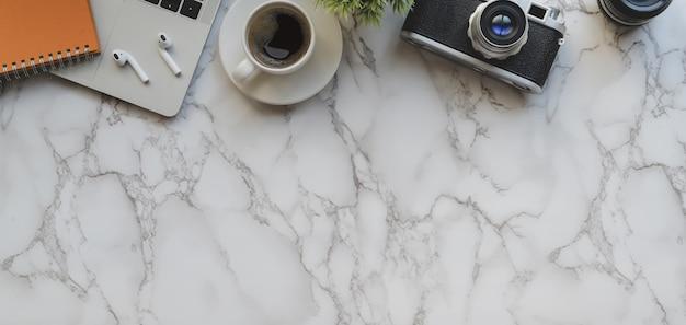 Widok z góry stylowy obszar roboczy fotografa z laptopem i materiały biurowe na marmurowym biurku