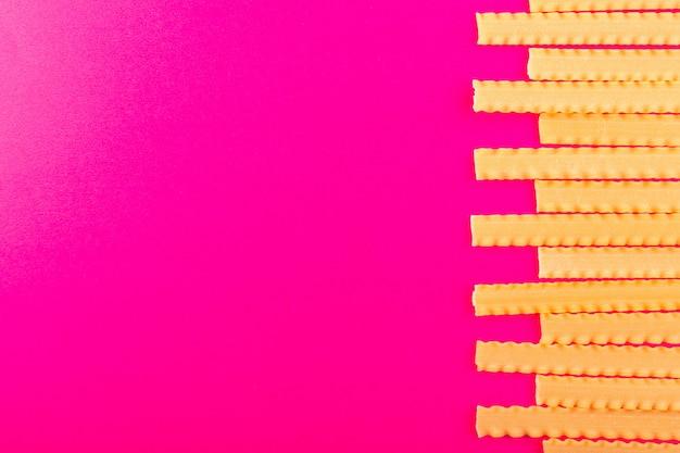 Widok z góry suchy włoski makaron długi surowy wyłożony na różowo