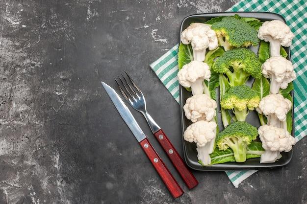 Widok z góry surowe brokuły i kalafior na czarnym prostokątnym talerzu na zielono-białej serwetce widelec i nóż na ciemnej powierzchni wolne miejsce