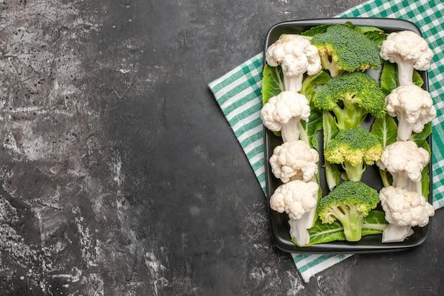 Widok z góry surowe brokuły i kalafior na czarnym prostokątnym talerzu na zielono-białej serwetce widelec i nóż na ciemnej wolnej powierzchni