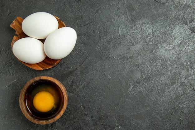Widok z góry surowe całe jaja na szarym tle jajko śniadanie posiłek surowe