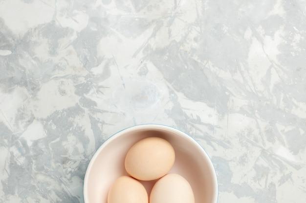 Widok z góry surowe całe jaja wewnątrz małego talerza na jasnobiałym tle zdjęcie surowego posiłku śniadanie rano