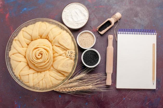 Widok z góry surowe ciasto okrągłe utworzone z notatnikiem na ciemnej powierzchni