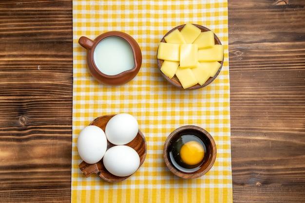 Widok z góry surowe jajka z pokrojonym serem i mlekiem na drewnianej powierzchni jaja produktowe ciasto mączka surowa żywność
