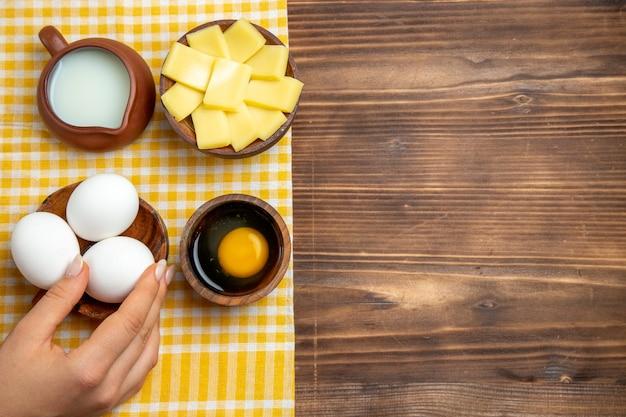Widok z góry surowe jajka z serem i mlekiem na drewnianym tle produkt jaja ciasto mączka surowe jedzenie
