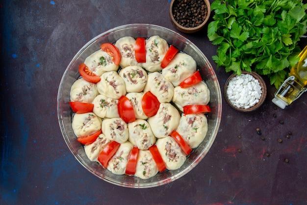 Widok z góry surowe kawałki ciasta z mielonym mięsem i świeżymi czerwonymi pomidorami na ciemnym posiłku kuchnia kolor jedzenie danie kuchnia zdjęcie