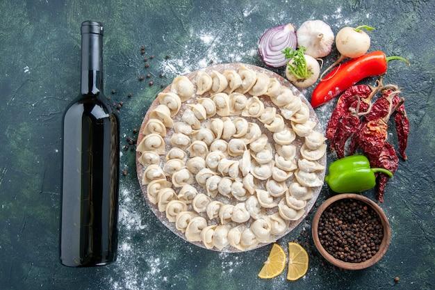 Widok z góry surowe małe pierogi z mąką i warzywami na ciemnym tle mięso ciasto jedzenie danie kaloryczny kolor warzywny posiłek