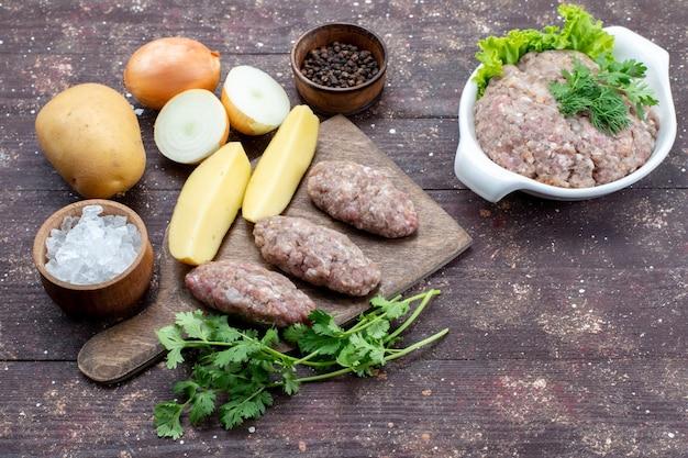 Widok z góry surowe mięso z surowymi ziemniakami sól cebula i zielenie na brązowym rustykalnym drewnianym biurku danie ziemniaczane posiłek obiad