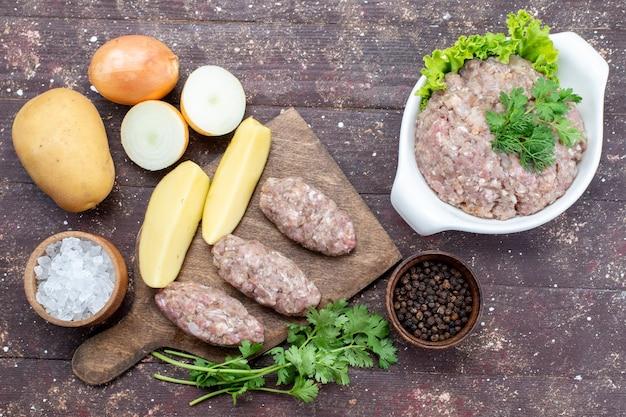 Widok z góry surowe mięso z surowymi ziemniakami sól cebula notatnik i zielenie na brązowym drewnianym biurku mięso danie ziemniaczane posiłek obiad