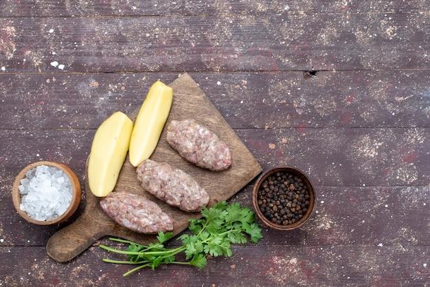 Widok z góry surowe mięso z surowymi ziemniakami, solą i zieleniną na brązowym biurku danie ziemniaczane danie obiadowe