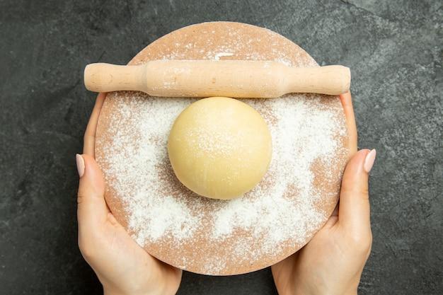 Widok z góry surowe okrągłe ciasto z mąką na szarym biurku ciasto surowa mąka z mąki spożywczej