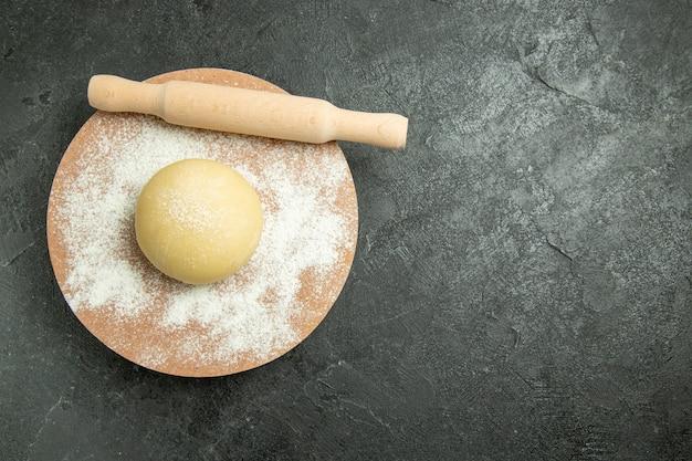 Widok z góry surowe okrągłe ciasto z mąką na szarym tle ciasto mączka surowa mąka żywnościowa