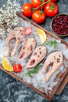 Widok z góry surowe plastry rybne z lodem na miskach na desce z pestkami granatu pomidory na stole