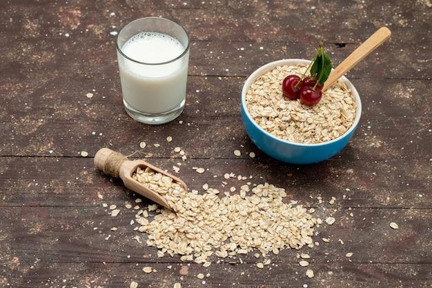 Widok z góry surowe płatki owsiane wewnątrz białej płytki z mlekiem na brązowym, surowym śniadaniu zdrowej żywności