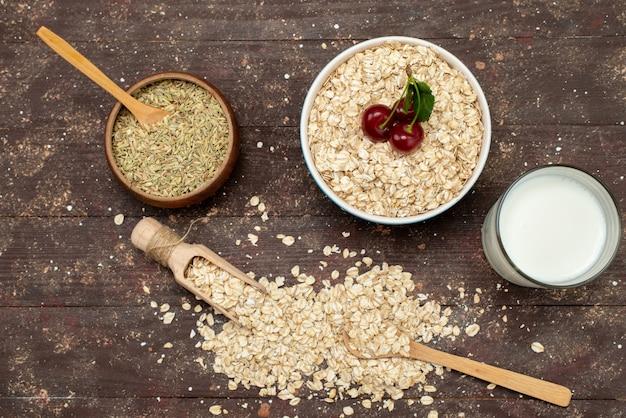 Widok z góry surowe płatki owsiane wewnątrz białej płyty na brązowym, z surowym zdrowym śniadaniem mleka