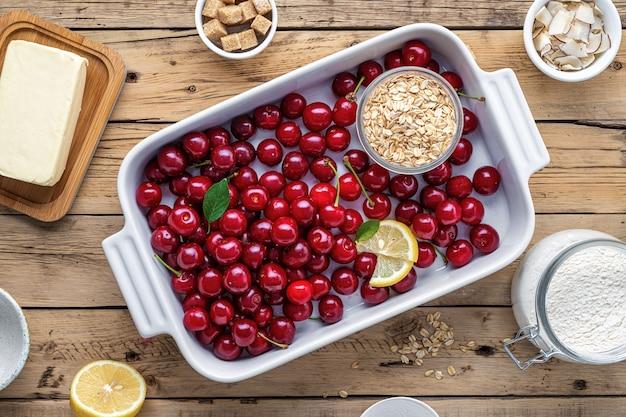 Widok z góry surowe składniki do gotowania ciasta wiśniowego na drewnianym stole