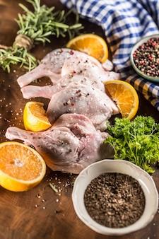 Widok z góry surowe udka z kaczki z pomarańczami ziołami rozmarynem sól kminkiem i pieprzem.