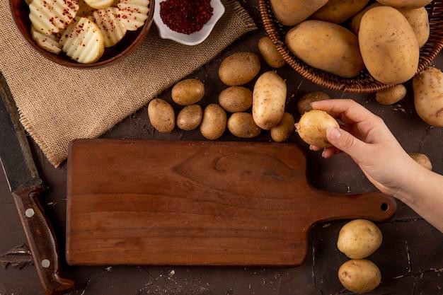 Widok z góry surowe ziemniaki w koszu i pokrojone ziemniaki z suszonymi płatkami chili w misce na brązowym tle