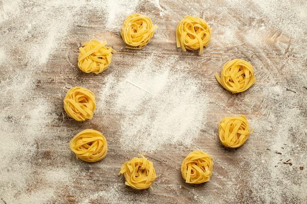 Widok z góry surowego ciasta makaronu kwiat utworzony z mąki na drewnianym tle ciasto posiłek makaronu żywnościowego
