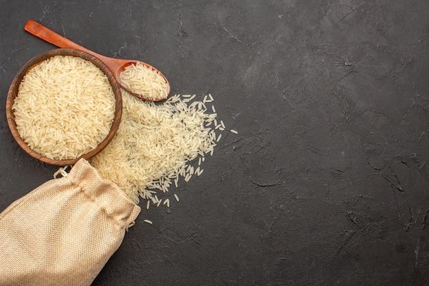 Widok z góry surowego ryżu wewnątrz brązowego talerza na szarej powierzchni