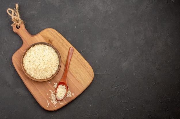 Widok z góry surowego ryżu wewnątrz drewnianego brązowego talerza na szarej powierzchni