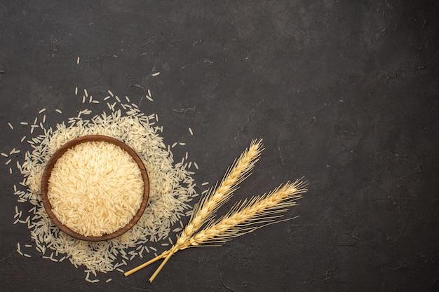 Widok z góry surowego ryżu wewnątrz talerza na ciemnoszarej powierzchni