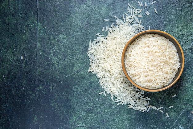 Widok z góry surowego ryżu wewnątrz talerza na ciemnym biurku