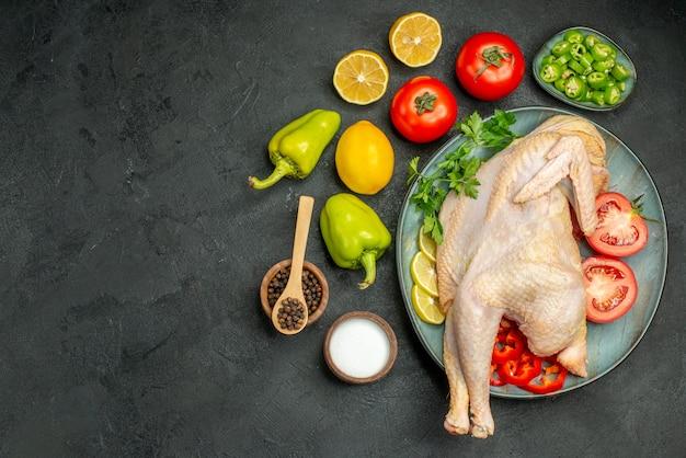 Widok z góry surowego świeżego kurczaka wewnątrz talerza z zieleniną cytryną i warzywami na ciemnym tle