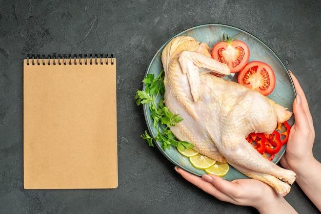Widok z góry surowego świeżego kurczaka wewnątrz talerza z zieleniną i warzywami na ciemnym tle