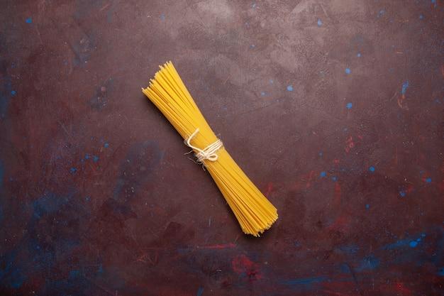 Widok z góry surowego włoskiego makaronu długo uformowanego na ciemnym tle mączka żywnościowego ciasta makaron surowy