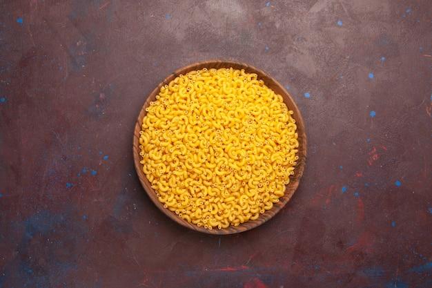 Widok z góry surowego włoskiego makaronu trochę utworzonego na ciemnym tle makaronu surowego mączki ciasta żywnościowego